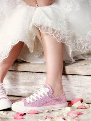 Wedding Dress and Pink Tennis Shoe Clad Body Sitting On Wooden Stairs . Elbows On Knees. Cute and Snappy.